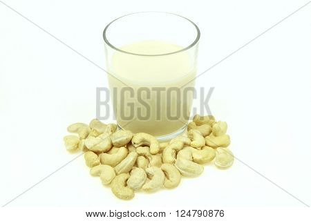 Heap of raw cashews and a glass of cashew milk, on white background.