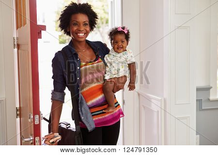 Young black woman holding child arriving home