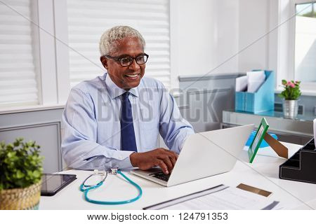 Senior black male doctor at work using laptop in an office