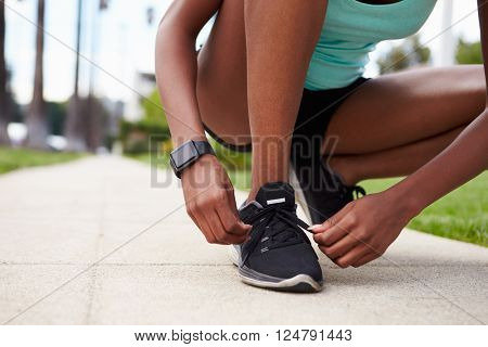 Young black woman tying sports shoes in the street
