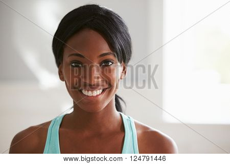 Head and shoulders portrait of smiling young black woman