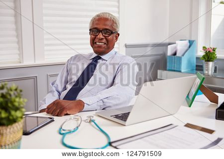 Senior black male doctor in an office looking to camera