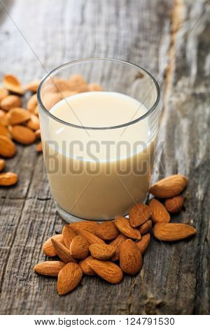Heap of almonds and a glass of almond milk, on wooden surface
