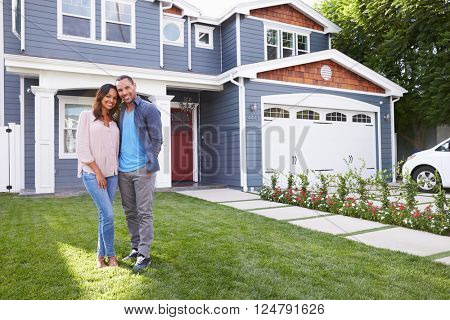 Happy black couple standing outside their house