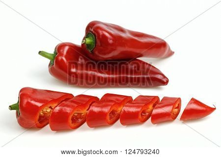 Pointy red peppers and one cut into pieces, on white background.