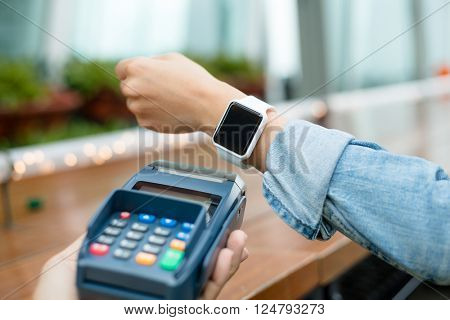 Woman using smart phone to pay by NFC technology