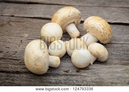 Stack of white button mushrooms, on wooden surface