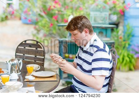 young man having breakfast outside in summer with various jams, bread, coffee, croissants, muesli and orange juice. French breakfast. Provence, France