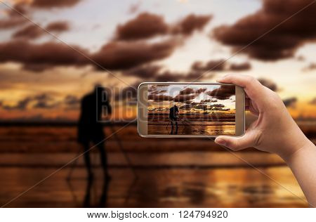 Hand of women shooting image with smart phone on blurred photographer and beach sunset in twilight