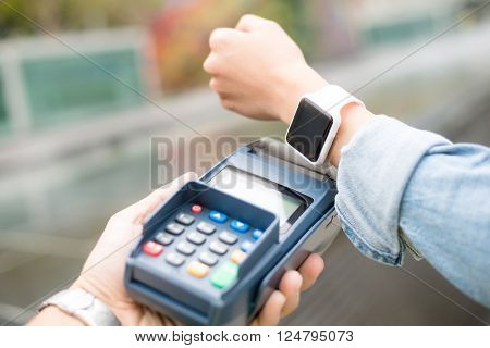 Woman pay on pos machine by NFC technology