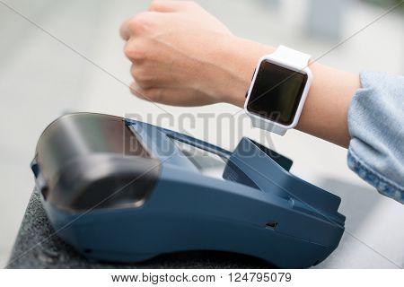 Woman using smart watch pay on pos machine