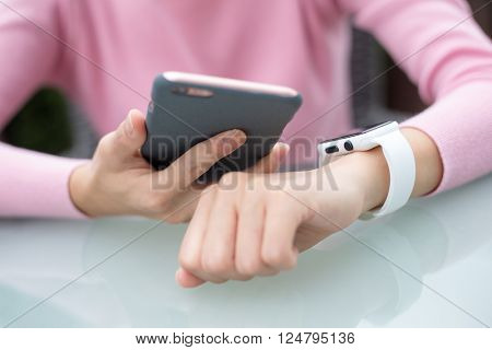 Woman using mobile phone to connect with smart watch