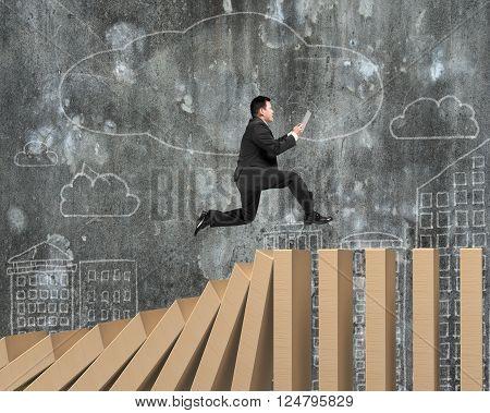 Man Using Digital Tablet Running On Falling Wooden Dominos