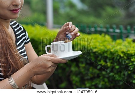 Woman drinking green tea in the morning in the garden without full face. The woman holding the tea cup in her hands and dipping the tea bag into it. She had brown hair and her face is not visible in the photograph