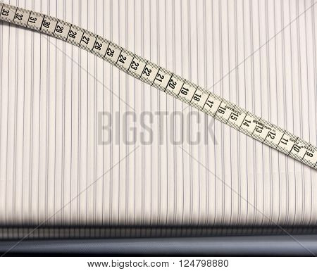 Tailor's White Tape Measure on Striped Cloth Material Swatches