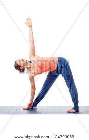 Beautiful sporty fit woman practices yoga asana utthita trikonasana - extended triangle pose isolated on white background