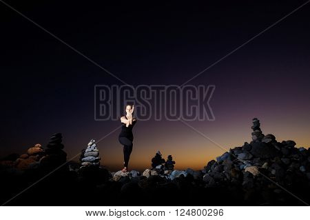 Summer sunset yoga session on beautiful Playa del Duque beach with stone pile stacks silhouettes - tropical Tenerife island, Canary in Spain. GARUDASANA, eagle pose