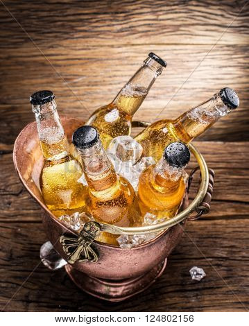Cold bottles of beer in the brazen bucket on the wooden table.