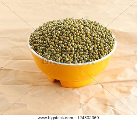 Mung beans in a bowl on a brown paper.
