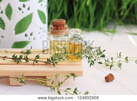Essential thyme oil in bottles. Aroma lamp, fresh green herbs.