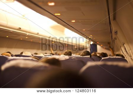 Interior airplane with passengers focus on passenger head.
