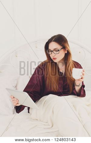 Young woman reads from tablet pc in bed. Girl in eyeglasses looks into gadget tablet pc. Morning coffee. Beautiful woman in nightwear at bed surfing internet at tablet computer. High key. Soft toning