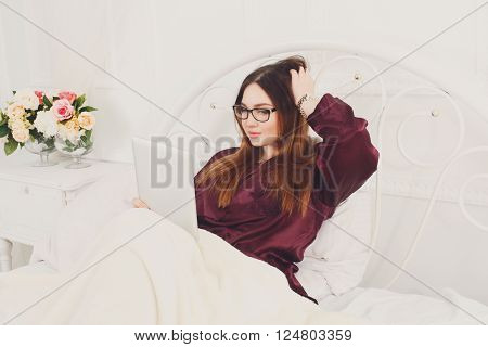 Young waking up woman with tablet pc in white bed. Girl in eyeglasses looks into gadget tablet pc. Morning coffee. Beautiful woman in nightwear at bed surfing internet at tablet computer. High key.