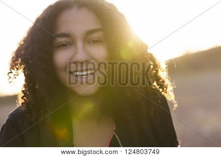 Beautiful happy mixed race African American girl teenager female young woman with perfect teeth smiling in golden light with sun flare at sunset or sunrise