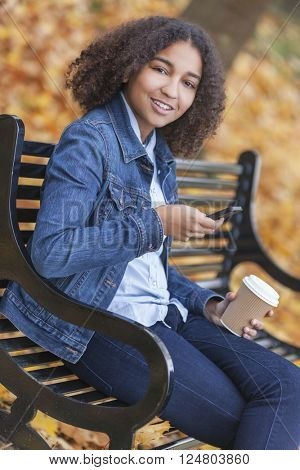 Happy mixed race African American girl teenager female young woman drinking takeaway coffee & texting on cell phone outside sitting on park bench in autumn or fall