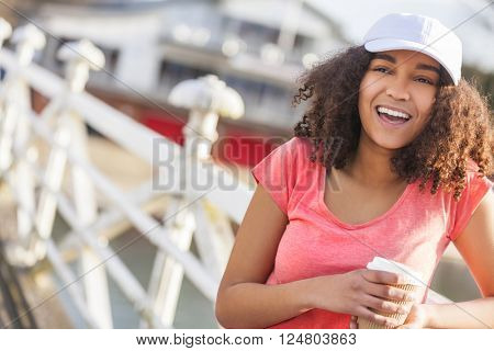 Beautiful happy mixed race African American girl teenager female young woman with perfect teeth smiling drinking takeaway coffee outside wearing white baseball cap and pink t-shirt