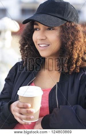 Beautiful happy mixed race African American girl teenager female young woman smiling drinking takeaway coffee outside wearing black baseball cap and bomber jacket