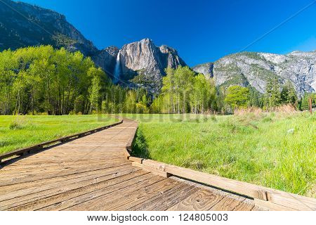 spring landscape with path to the waterfall