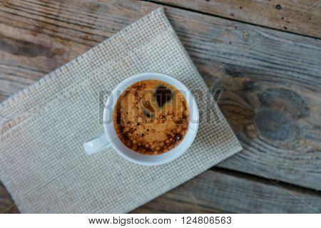 White cup of espresso macchiato on old wooden table. Cup of Espresso - stock photo.