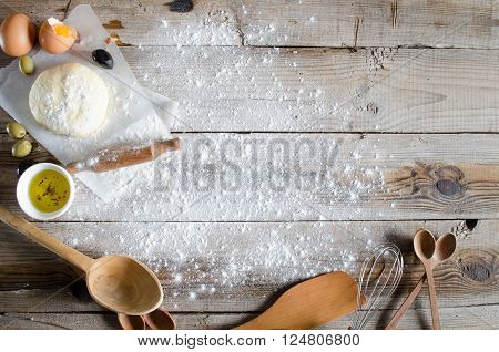 Making pie: Dough rolling-pin and wheat flour on wooden table