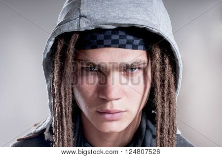 Portrait of serious man with dreadlocks and wearing a hood over gray background.