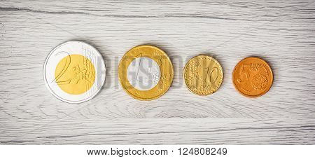 Chocolate money on the wooden background. Euros and cents. European currency.