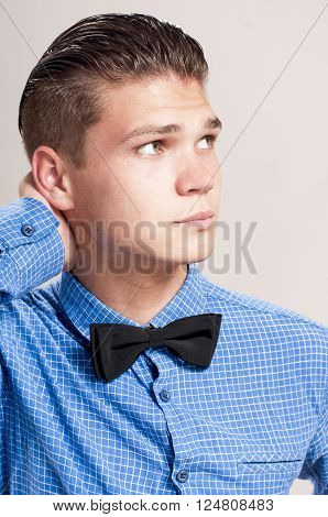 Profile of gallant man in the blue shirt with black bow tie.