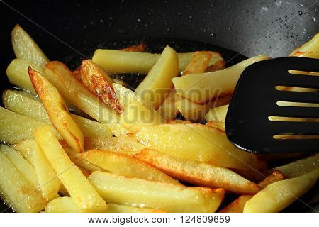 Young potatoes fried in boiling oil to a frying pan