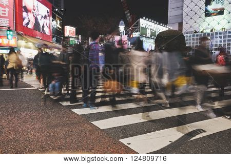 TOKYO, JAPAN - MARCH 29, 2016: Shibuya Crossing,Crowd of citizens start walking across roads. The world famous crossroad in Shibuya, Tokyo with commuters at night.