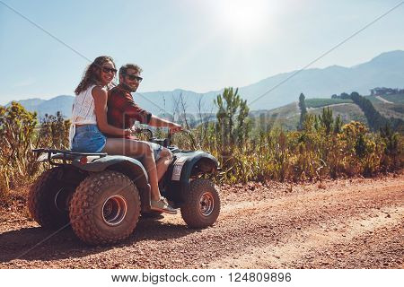 Portrait of loving couple in nature on a off road vehicle. Young man and woman enjoying a quad bike ride in countryside.