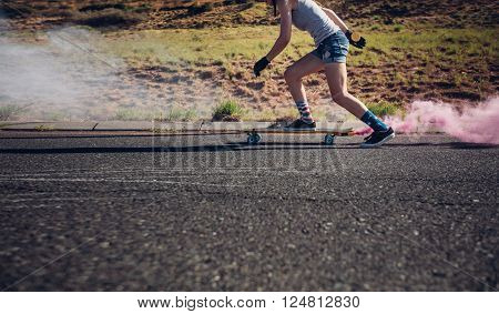 Cropped shot of young woman longboarding down the road. Side view of female practicing  skating. Skate board with color smoke grenade.