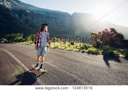 Young man longboarding outdoors on rural road. Male skateboarding on a summer day.