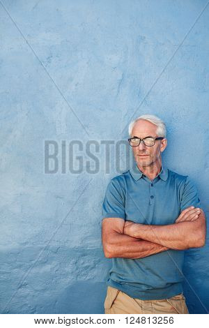 Mature Man With Glasses Against A Blue Wall