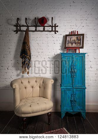 Retro composition of vintage beige armchair vintage blue cupboard wall hanger with ornate scarf and red fez and framed painting in studio