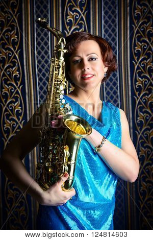 Beautiful actress with saxophone standing by a vintage wallpaper. Professional musician.