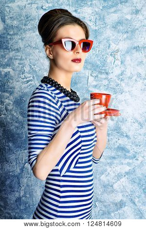 Fashionable lady in elegant dress and pin-up hairstyle posing at studio. Pin-up glasses, optics style. Beauty, fashion concept.