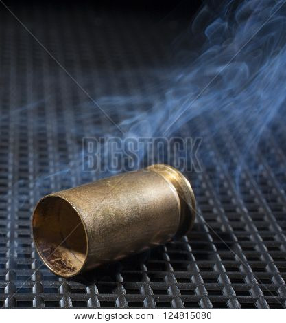 Brass from a semi automatic pistol with smoke around ** Note: Visible grain at 100%, best at smaller sizes