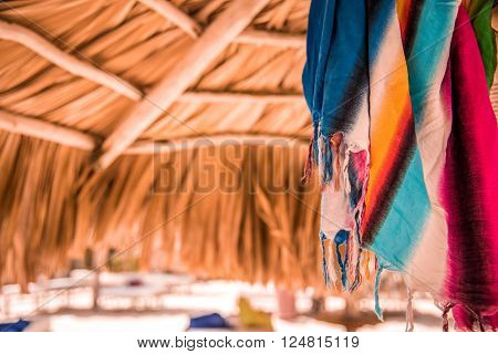 Bright multicolored pareo under sunshade from palm leaves, toned