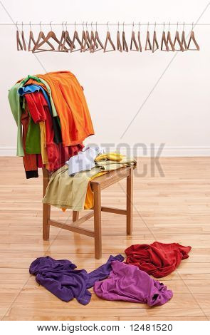 Messy Clothes On A Chair And Empty Hangers On The Background