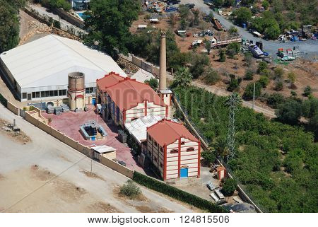 ALORA, SPAIN - JUNE 27, 2008 - Elevated view of an old fashioned factory with chimney in valley Alora Malaga Province Andalucia Spain Western Europe, June 27, 2008.